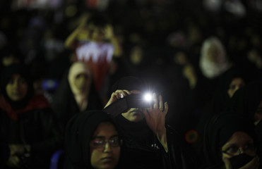 A female protester takes pictures with her phone as she attends an anti-government protest held by Al-Wefaq in occasion of Labour Day in Budaiya