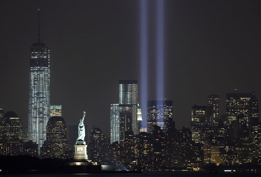 The Tribute in Light is illuminated next to the Statue of Liberty and One World Trade Center during events marking the 12th anniversary of the 9/11 attacks on the World Trade Center in New York