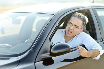 Road rage concept - irritated man screams and gestures while driving the car