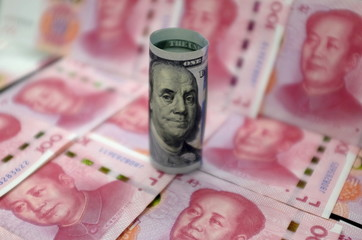 Benjamin Franklin U.S. 100-dollar banknote and Chinese 100-yuan banknotes depicting the late Chinese Chairman Mao Zedong, are seen in a picture illustration in Beijing