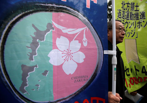 A protester holding a flag featuring map of  disputed islands claimed by both Japan and Russia, called the Northern Territories in Japan and the Southern Kuriles in Russia, as they demand their return during a rally in Tokyo, Japan