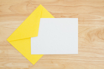 An embossed blank white card with yellow envelope on a desk