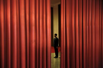 A security agent guards the area behind curtains inside the Great Hall of the People where sessions of the National People's Congress (NPC) are taking place, in Beijing