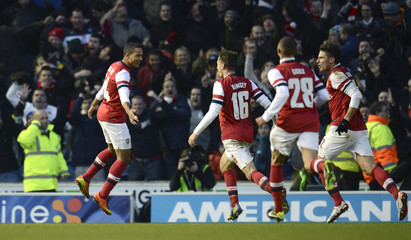 Arsenal's Walcott leaps and celebrates after scoring his team's third goal during their FA Cup fourth round soccer match against Brighton and Hove Albion in Brighton