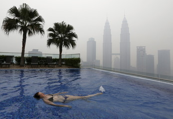 Woman swims in a rooftop pool in front of the Petronas Towers, shrouded by haze, in Kuala Lumpur, Malaysia