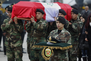 A police officer carries a police hat of one of two fellow officers who were killed in an ambush, during a ceremony at the police airport in Lima