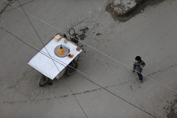 A boy walks near lupine seeds snacks displayed for sale on a cart in the rebel held besieged city of Douma, a suburb of Damascus