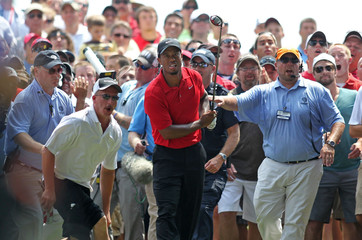 Tiger Woods of the U.S. and the crowd behind him watch his second shot from the rough on the 16th hole at Firestone Country Club in Akron