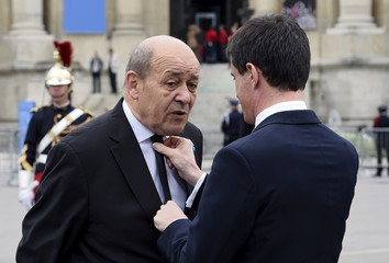 French Prime Minister Valls adjusts Defence minister Le Drian's tie before attending a ceremony to mark 70 years since the victory over Nazi Germany during World War II at the statue of former President de Gaulle in Paris