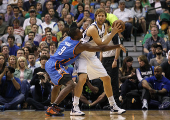 Dallas Mavericks Nowitzki works for a shot against Oklahoma City Thunder Ibaka during NBA game in Dallas, Texas