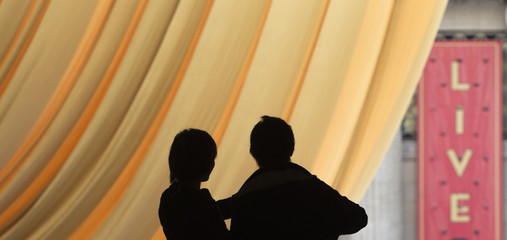 Couple is silhouetted against a golden drape overlooking red carpet preparations ahead of the 85th Academy Awards in Los Angeles, California