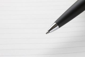 黒いボールペンのペン先、罫線入りのノートの背景