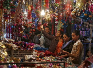 Women shop for Christmas decorations at a roadside market in Ahmedabad