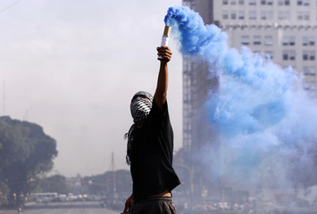 A masked protester lights a flare during a demonstration to commemorate the 10th anniversary of social and economic chaos that led to Fernando de la Rua's resignation of the presidency in Buenos Aires