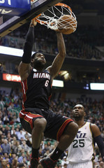Miami Heat forward James gets past Utah Jazz center Jefferson for a dunk during the first half of their NBA basketball game in Salt Lake City