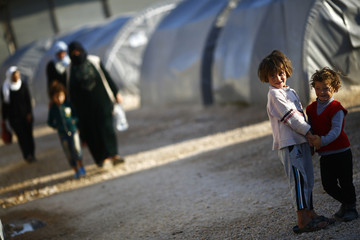 Kurdish refugee children from the Syrian town of Kobani look on in a camp in the southeastern town of Suruc