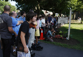 Spectators and journalists watch as guests of the Chelsea Clinton Marc Mezinsky wedding begin to depart in Rhinebeck