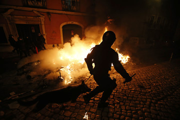 A policeman runs in front of a burning barricade during clashes near the Parliament in Lisbon