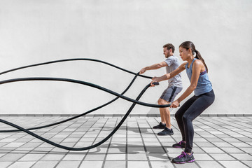 Fitness people exercising with battle ropes at gym. Woman and man couple training together doing battling rope workout working out arms and cardio for crossfit exercises.