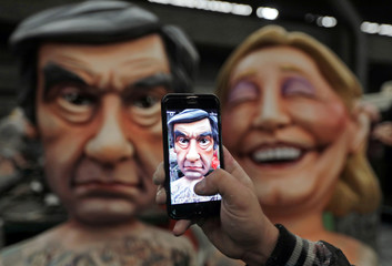 A worker takes a photo of a giant figure of Francois Fillon, member of Les Republicains political party and 2017 presidential candidate of the French centre-right, during preparations for the carnival parade in Nice