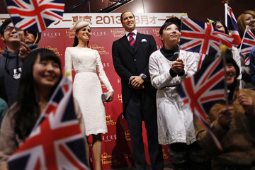 Guests pose with wax figures of Britain's Prince William and his wife Catherine, Duchess of Cambridge, during a media briefing at the Madame Tussauds Tokyo museum