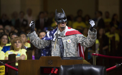 A person wearing a Batman mask speaks prior to a City Council vote to increase minimum wage at City Hall in Los Angeles