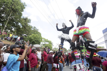 Onlookers use mobile phones to take pictures of members of the Kaisoca Moco Jumbies as they take part in the annual Labour Day celebrations, observed as a national holiday, along Fyzabad's Main Road, south of the city of San Fernando