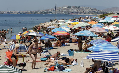 People enjoy the sunny weather on the beach of Alimos