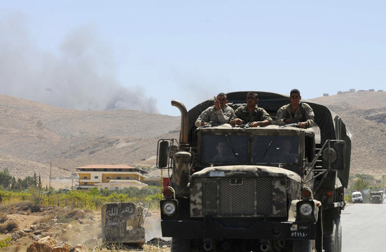 Lebanese army soldiers ride on military pick-up truck at entrance of the Sunni Muslim border town of Arsal, in eastern Bekaa Valley, as smoke rises in background during clashes between Lebanese army soldiers and Islamist militants