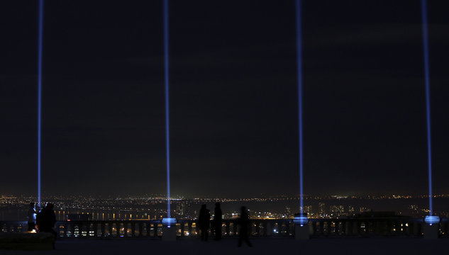 Blue beams of light are projected following a vigil  to remember the victims of a mass shooting in Montreal