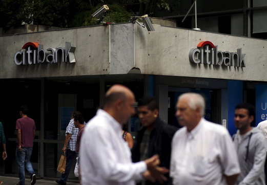 Two men talk as other people walk by a Citibank branch in Buenos Aires
