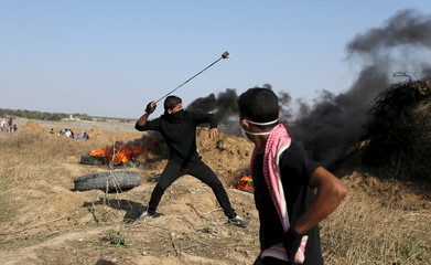 Palestinian protester uses a sling to hurl stones at Israeli troops during clashes near the border between Israel and Central Gaza Strip