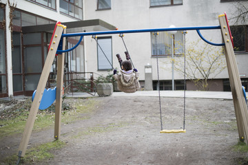 Migrant girl plays on swing outside of a refugee shelter which focuses on women and families in Berlin