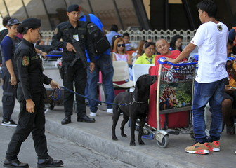 Members of the Philippine National Police (PNP) aviation security group with a sniffing dog inspect baggages of the airline passenger outside of the Ninoy Aquino International Airport in Manila