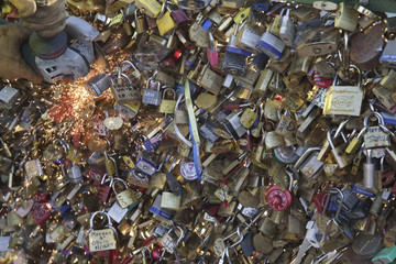 An employee of Paris city Hall removes padlocks clipped by lovers on the fence of the Pont des Arts over the River Seine in Paris