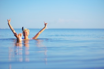 Happy young blonde girl with raised hands and feet above the water, eyes closed against pleasure, adopts procedures during summer vacation.