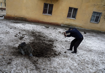 A local resident takes pictures of the remains of a rocket shell on a street in the town of Kramatorsk