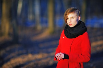 Portrait of a young serious girl with a stylish haircut in a red coat and black scarf at the neck, posing in the bright sun on a blurred background of trees in the Park, closeup.