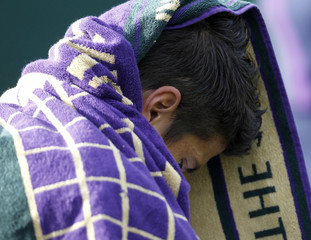 Fernando Verdasco of Spain sits with his towel over his head during his match against Robin Haase of the Netherlands at the Wimbledon tennis championships in London