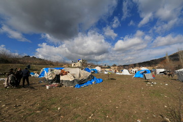 People stand outside tents housing internally displaced people in the town of Khirbet Al-Joz, in Latakia countryside, near the Syrian-Turkish border