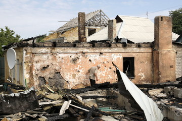 Man inspects debris while standing outside damaged house which according to locals was caused by recent shelling in Donetsk