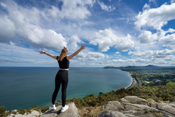 young beautiful girl female model photographer posing on top of the hill people embracing nature with open arms sea clouds blue sky tripod camera backpack sport clothes