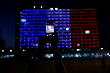 An Israel woman takes a picture of the Tel Aviv city hall as it is lit up in the colors of the French flag in tribute to the attack victims of Nice