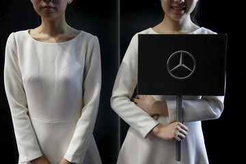 A hostess holds a Mercedes sign during a world premiere ceremony for the new Mercedes Benz E-Class Long Wheelbase in Beijing