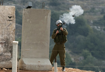 An Israeli soldier fires tear gas during a protest in Nilin