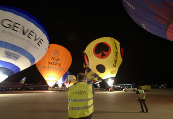 Photographers take pictures of hot air balloons during the night glow event of the sixth Montgolfiades Festival at Cointrin International Airport in Geneva