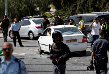 Israeli police and emergency personnel stand next to a car covered with bullet holes after Israeli police killed an Arab assailant who fired from the car wounding several people in Jerusalem