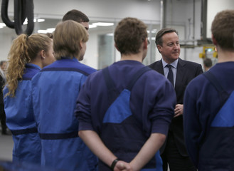 Britain's Prime Minister Cameron talks to trainees during visit at BMW manufacturing plant in Munich