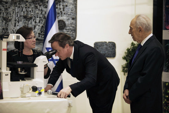 British Prime Minister Cameron looks through a microscope while Israel's President Shimon Peres stands next to him during their meeting in Jerusalem