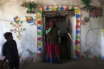 Tulsi, who is cotton picker, stands in the doorway of her room which is decorated with coloured patterns, in Meeran Pur village, north of Karachi